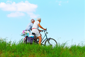 Older man and woman cycling in the countryside